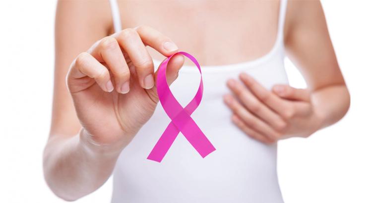 Mulher segurando o laço símbolo do Outubro Rosa mês de conscientização sobre o câncer de mama