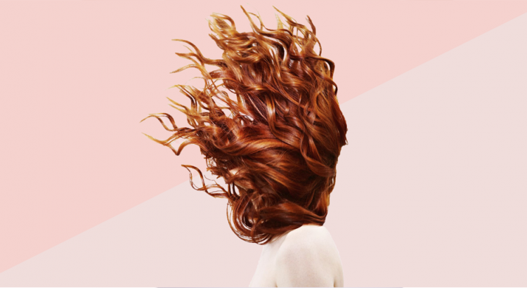 Mulher jogando o cabelo para cima em um fundo rosa