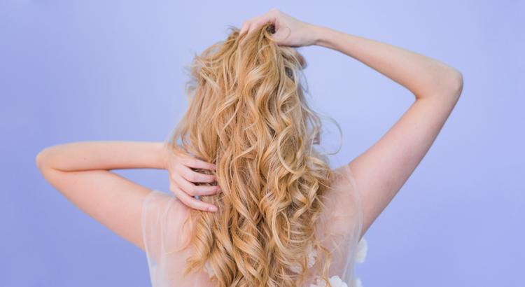 Mulher de cabelo loiro ondulado na frente de um fundo roxo
