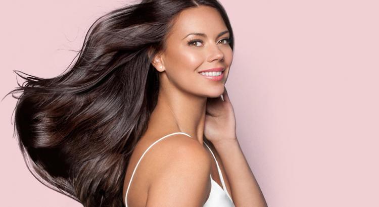 Mulher com o cabelo hidratado na frente de um fundo rosa