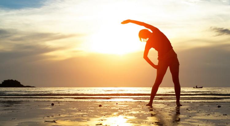Pessoa na praia em frente ao pôr do sol fazendo alongamento