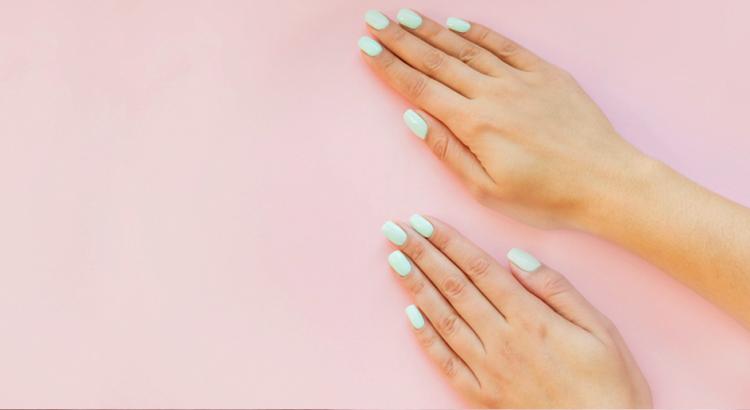 Mão com unhas azul claro em um fundo rosa
